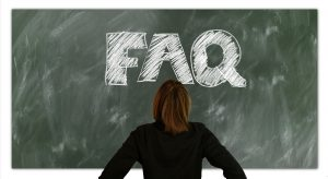"Woman looking at the letters ""FAQ"" (frequently asked questions) written on a chalkboard."