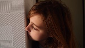 "Woman peeking around a corner to illustrate ""spying."""