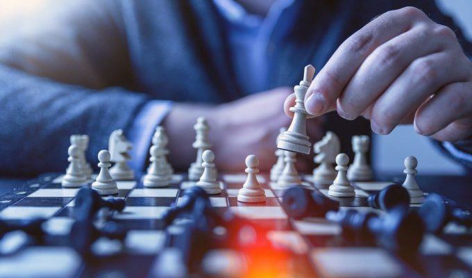 Person playing chess to illustrate how to develop a content marketing strategy.